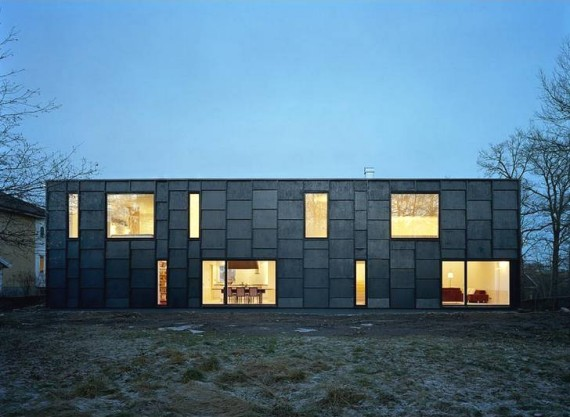 A modern black house with large windows.