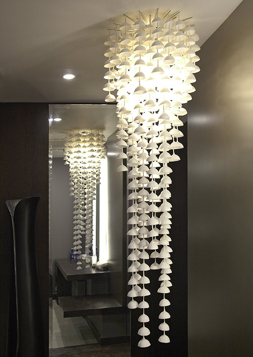 A sculptural chandlier made from hundreds of thin bone china bells, creates delicate chiming tones when activated by gentle motion.
