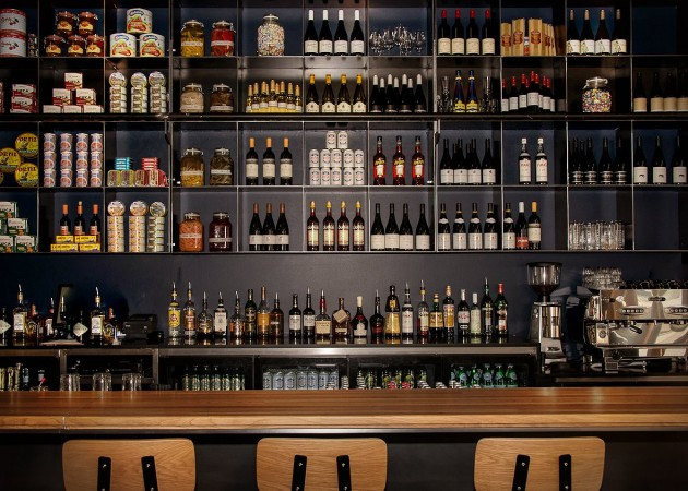 The wall behind this bar in a restaurant is full of cubes, perfect for storing food and drink items.