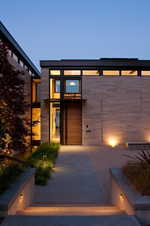 Lighting highlights the landscaping around this home.