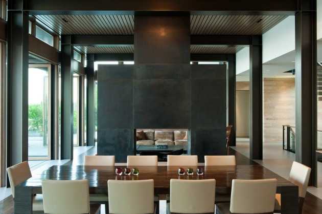 A see-through fireplace with a steel surround separates the living area from the dining area.