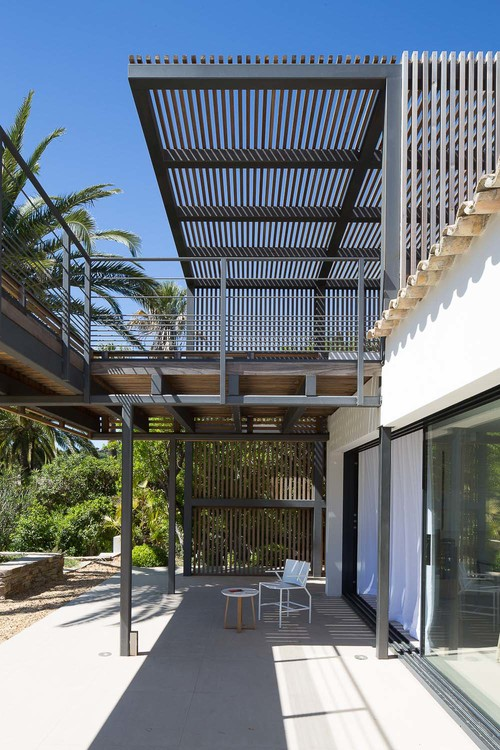 A pergola on the second floor of this home provides shade to the lower level.