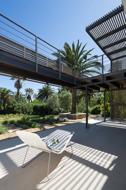 A walkway on a higher level provides shade for the lower outdoor spaces.