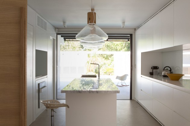 This smaller white kitchen has a central long island with pendant lights hanging above.