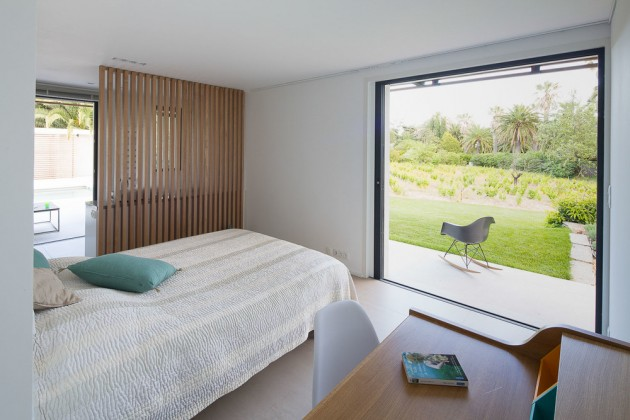 This bedroom has a large window with views of the backyard.