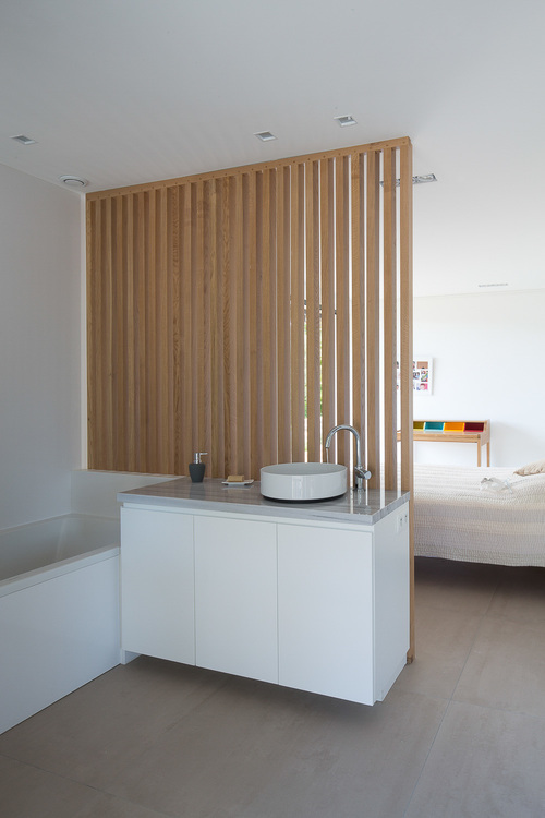 This ensuite bathroom is partitioned from the bed with a wooden slat wall.