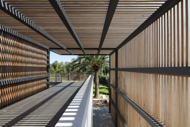A wooden slat pergola provides shade for this home in Saint Tropez.