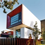 A window framed in Corten steel greets the street in front of this house