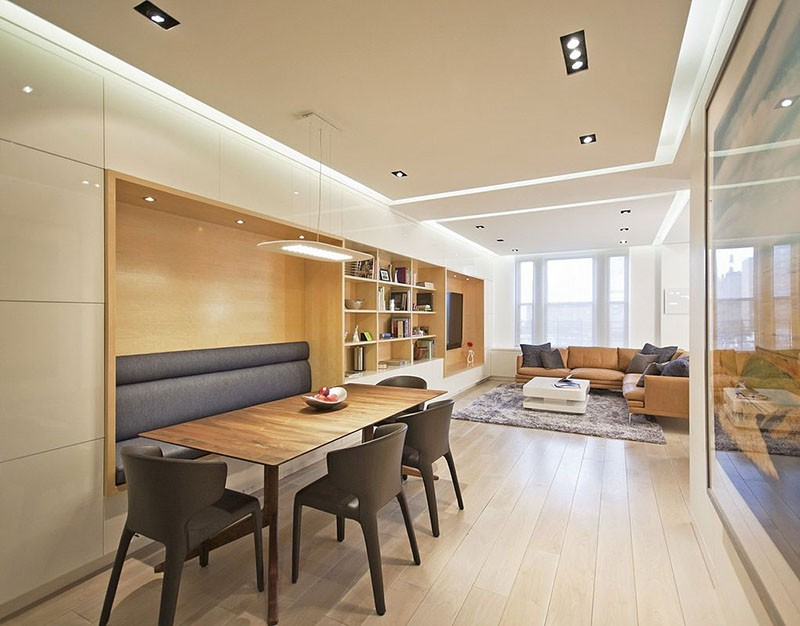 Built-in banquette seating for a dining table that flows into shelving.