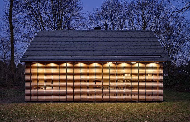 Windows with wood slat shutters line the side wall of this modern cottage, creating an open feeling, while at night, the shutters can be closed for more privacy.