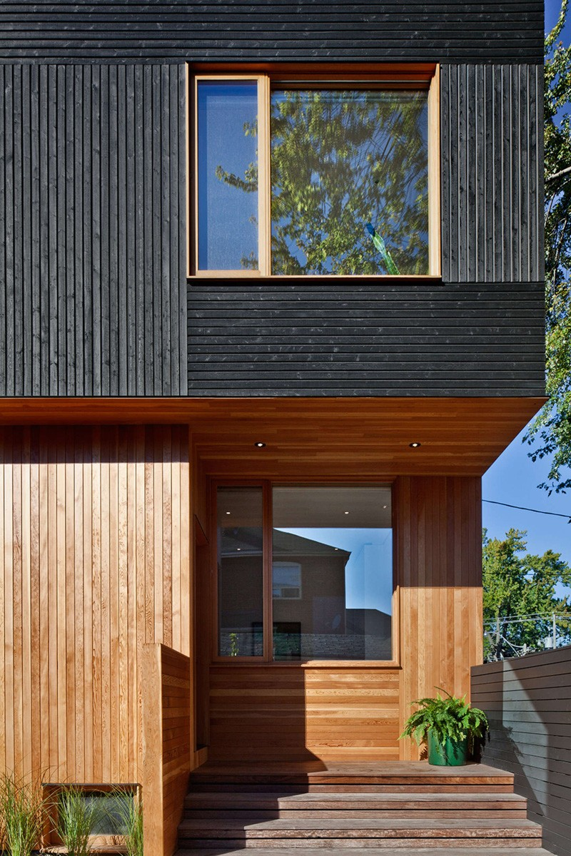 Black siding with natural wood accents for this toronto for Bardage de facade maison