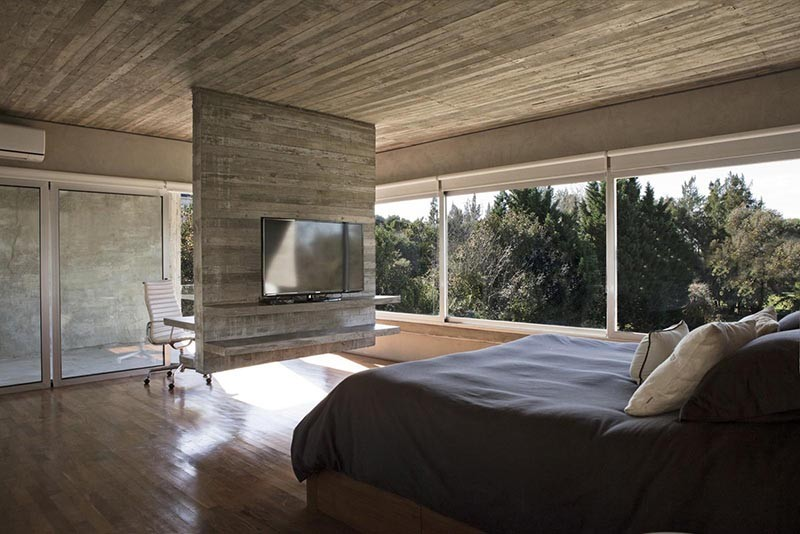 Hanging concrete room divider with a television on one side, and a desk on the other.