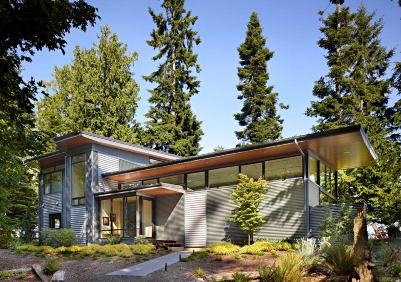 this pacific northwest house is located on a wooded waterfront
