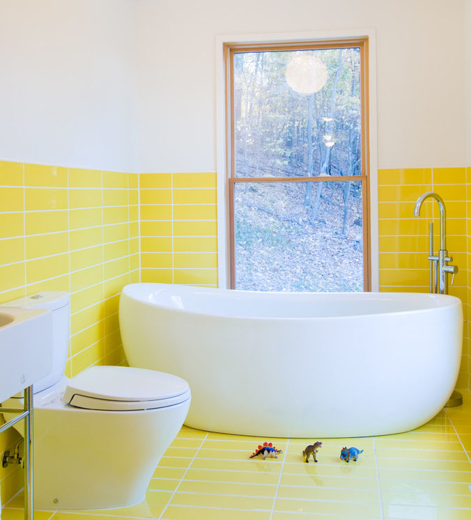 Yellow tiles on the floor and wall of this bathroom