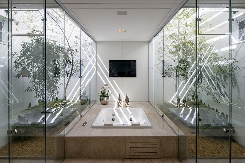A Bathtub Surrounded By A Glass Enclosed Garden