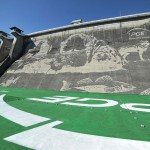 A mural has been done on the side of this dam by washing away layers of dirt