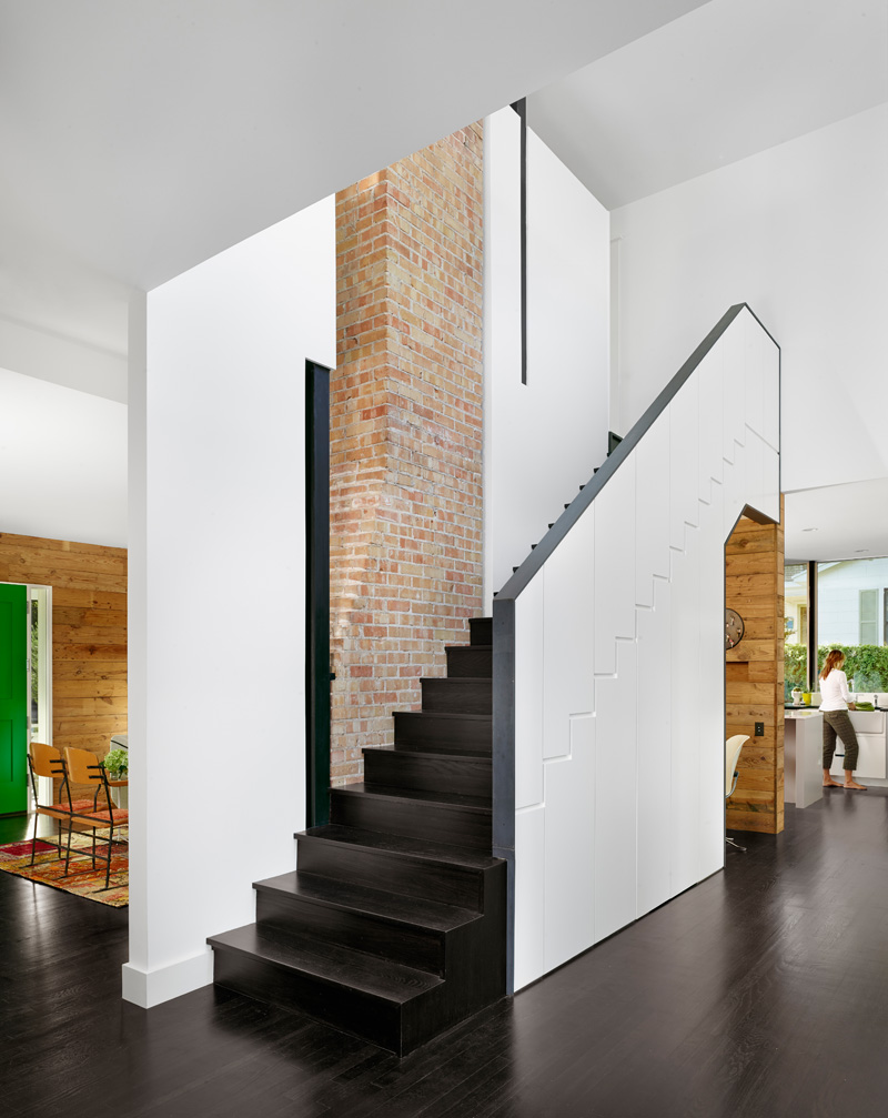 Dark wood stairs with a white exterior have have built-in hidden storage and an office nook.