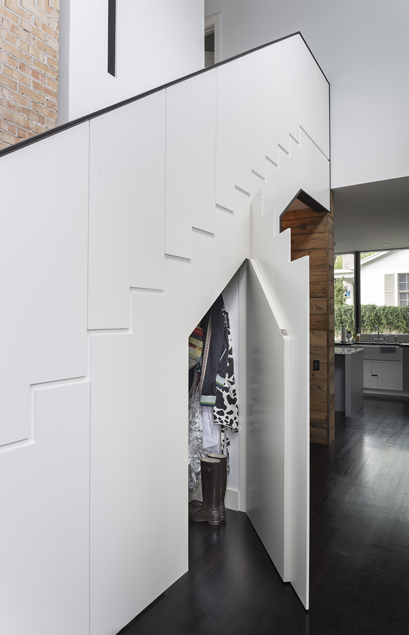 Hardware free cabinets under the stairs provide space for storing coats and shoes.