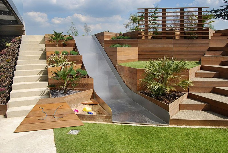 A Backyard Slide Among Terraced Planters