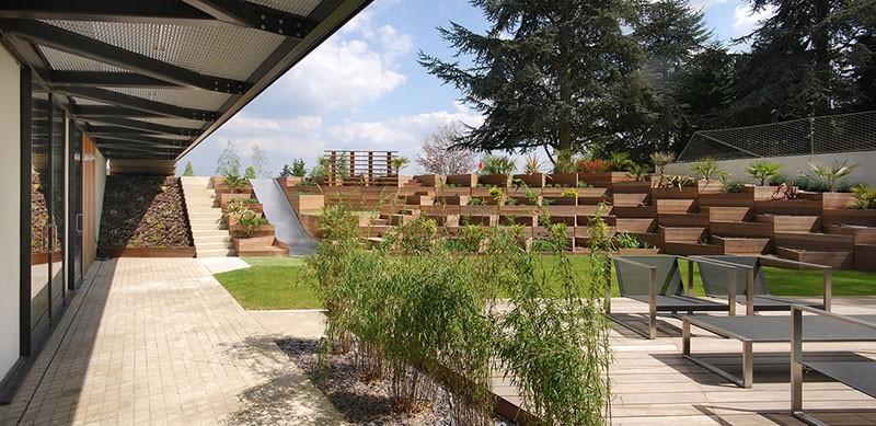 A Backyard Slide Among Terraced Planters