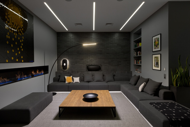 A dark living room with built-in shelving, a linear fireplace, and a couch that wraps around the corner. #LivingRoomIdeas #ModernLivingRoom