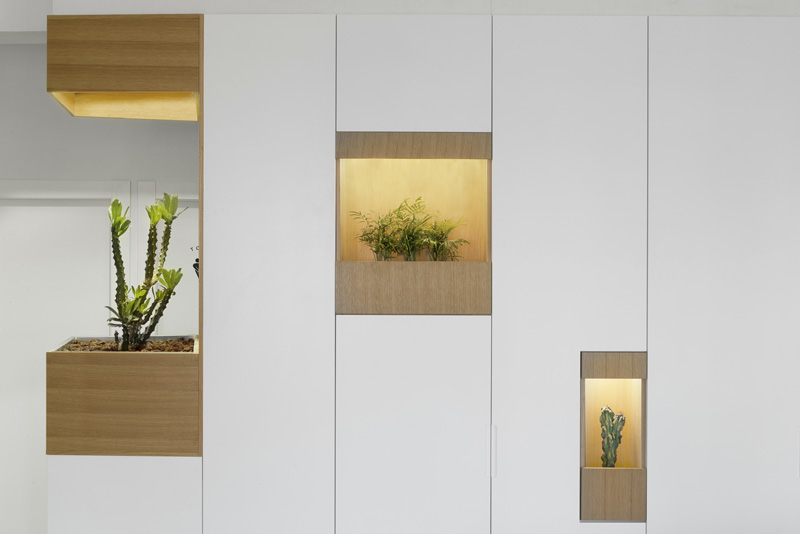 Pockets Of Plants Have Been Added To This White Wall Of Cabinets
