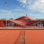 The roof of this tennis clubhouse dips down to create seating for spectators