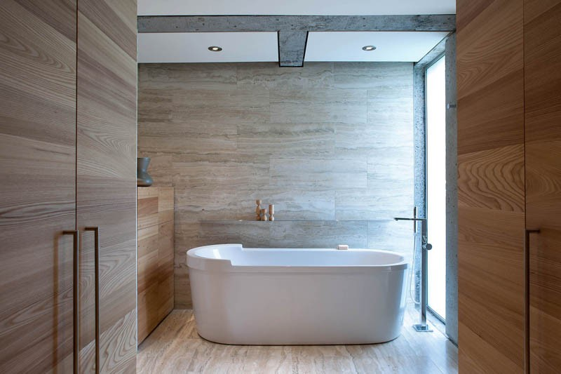 A standalone bathtub sits in a contemporary bathroom next to a limestone wall