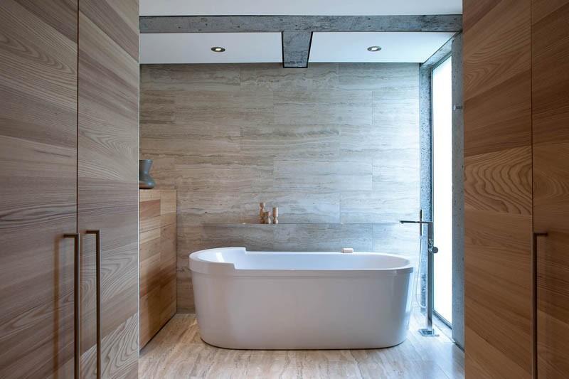 A standalone bathtub sits in a contemporary bathroom next to a limestone wall