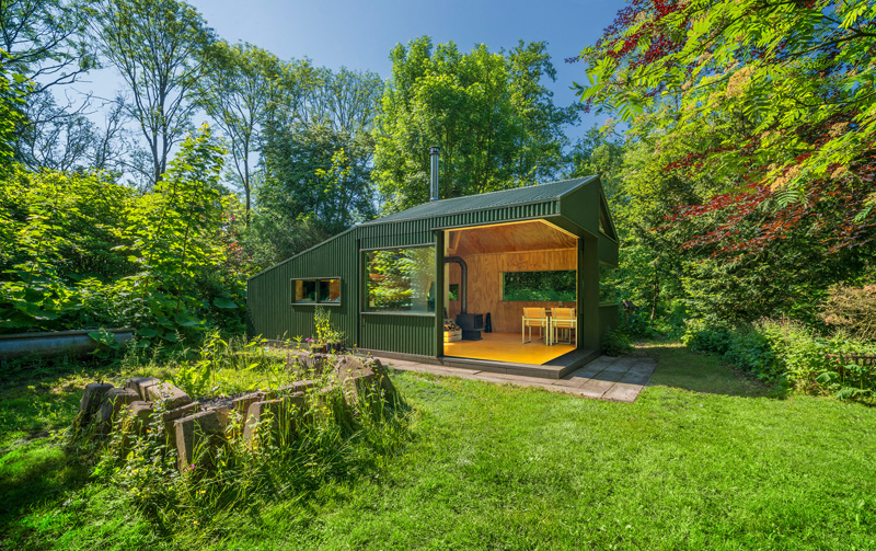 A small cabin with a green exterior and a wood-lined interior.