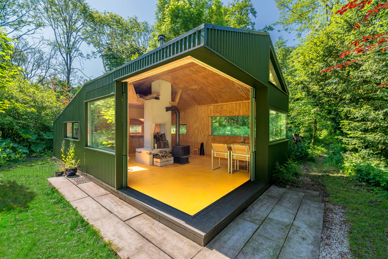 A small cabin with sliding doors that open up to a garden.