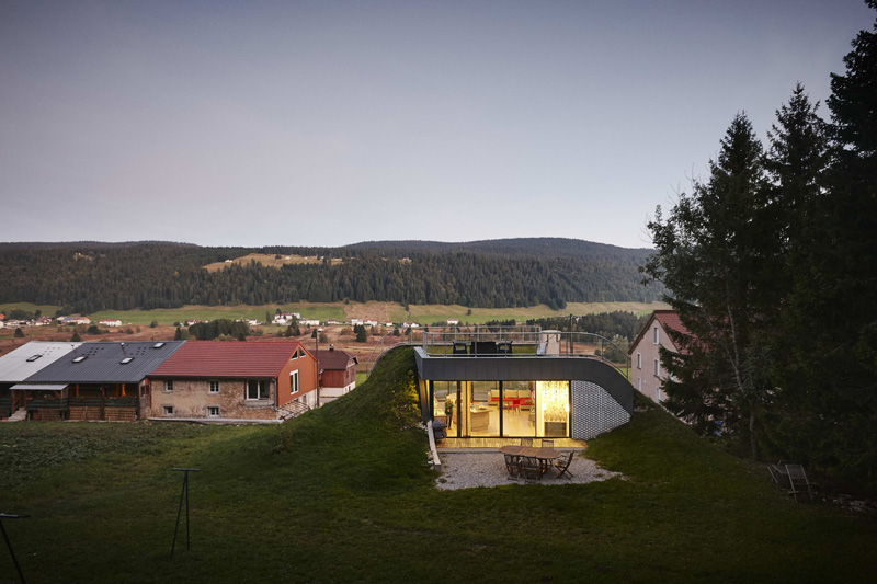 The balcony of a French house built into a hill, at dusk