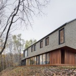 This cedar shingled house is at home surrounded by the forest in Quebec