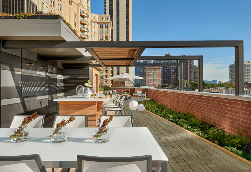 7 Design Lessons To Learn From This Awesome Roof Deck In Chicago // Think about including some shade -- They built a pergola above the kitchen area, and umbrellas have been used throughout the rest of the deck for additional shade protection.