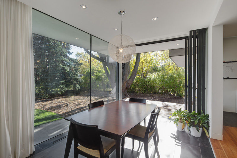 The backyard of this home is accessible through a wall of glass doors next to this dining room.