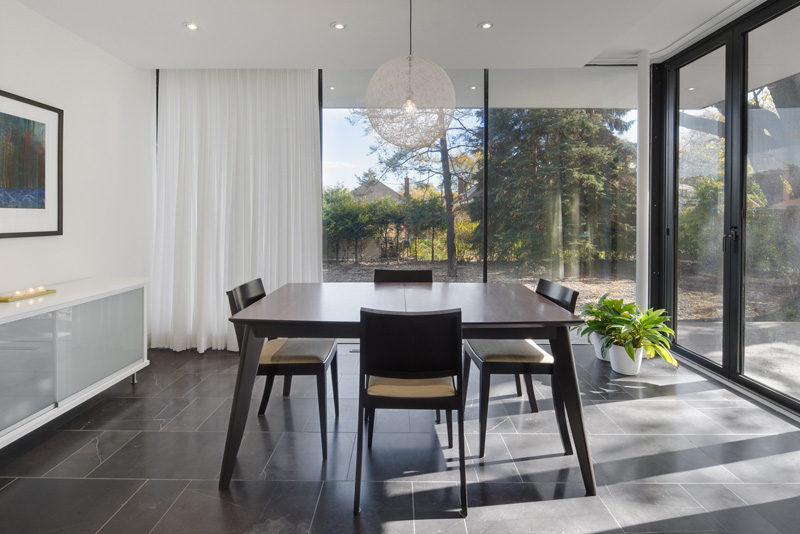 This dining room has view of the backyard through the floor-to-ceiling windows.