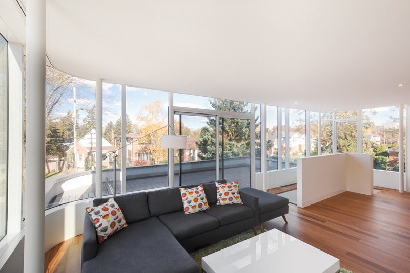 This living space with balcony access, takes advantage of the views with wrap-around windows.