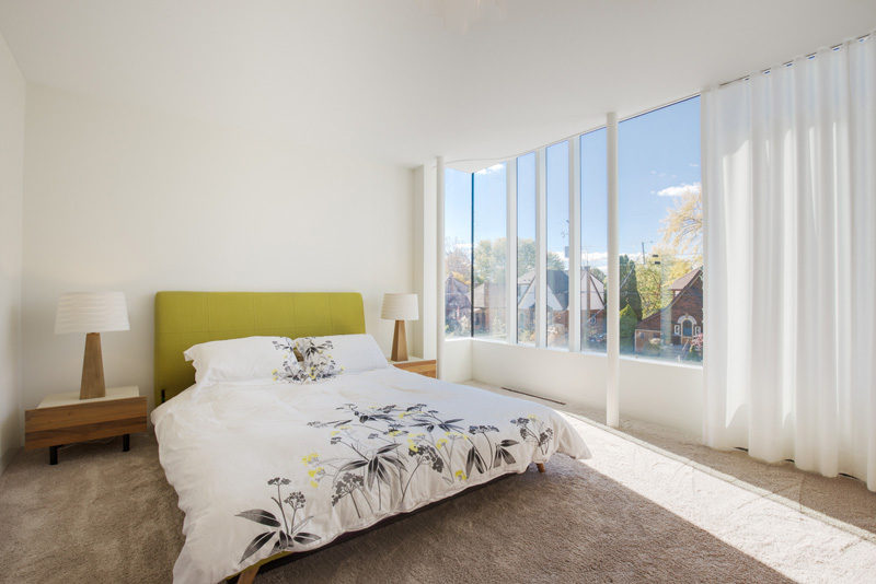 This bedroom has a wall of windows with a sheer white curtain.