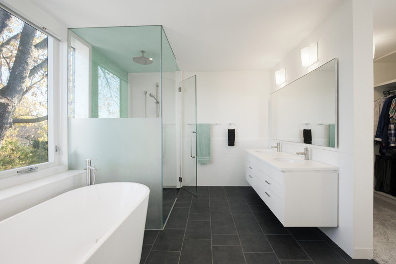 This bathroom has a walk-in shower with rainfall showerhead, a standalone bathtub, and a vanity with double sinks.
