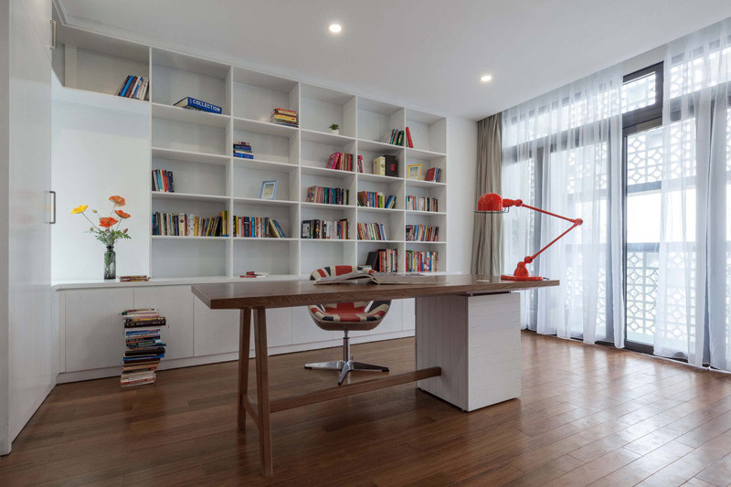 A modern home office with built-in shelving that lines the wall. #WhiteShelving #BuiltIShelving #Bookcase #WhiteBookshelf