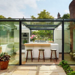This thatched cottage got a glass box extension for the kitchen