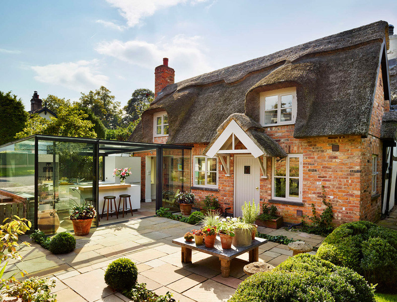 This thatched cottage got a glass box extension