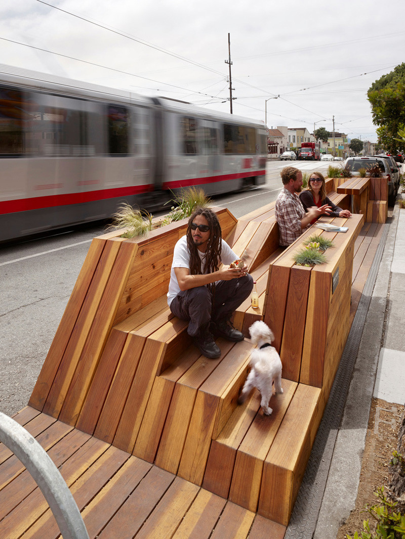 This parklet in San Francisco, California was designed by INTERSTICE Architects and includes four separate areas, including built in seating and tables, a bicycle rack - complete with air pump station, a children's play area, and a dog watering station with convenient spots to tie their leashes.