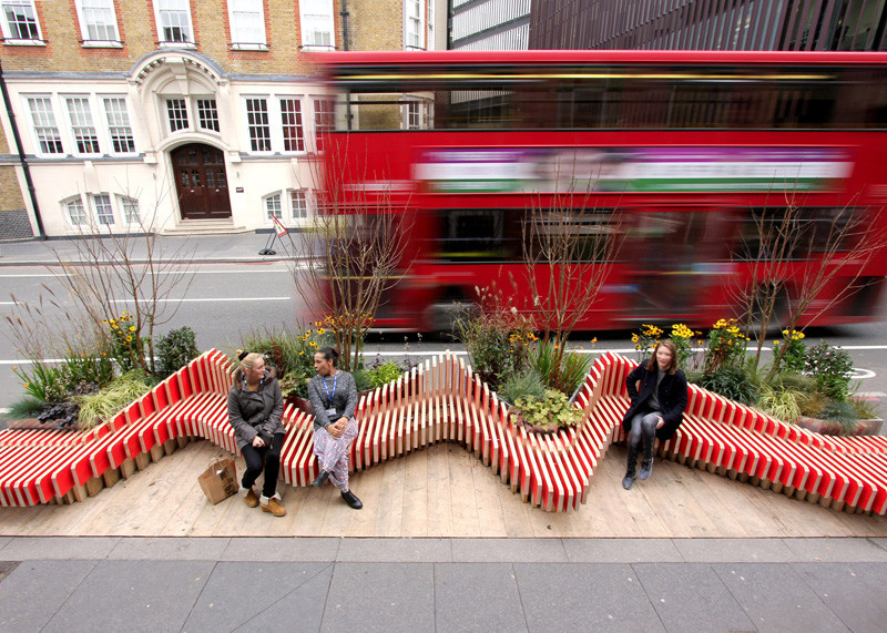 This parklet in London, England, designed by WMB Studio is made from wood that's been painted bright red and serves as a spot for people to gather, take a break from their day, and has air quality monitors built into it.