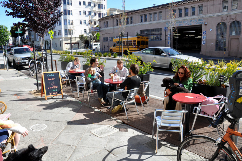 Wood planks have been laid down next to the sidewalk in San Francisco and planters have been added to create a casual patio space that can be enjoyed by people just walking by or by people eating at the cafe.