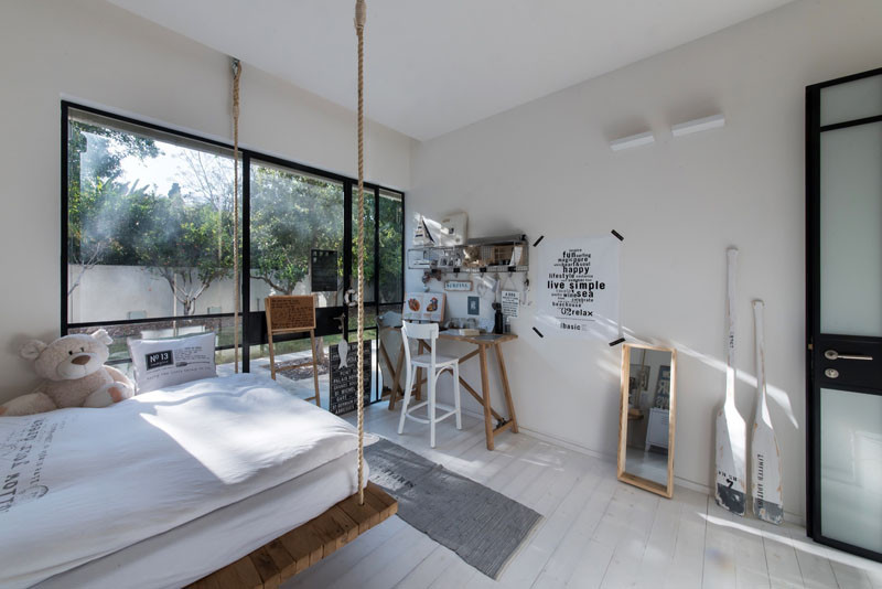 This hanging bed in a children's bedroom, is located inside a home in Tel Aviv, Israel, that has been designed by Neuman Hayner Architects.