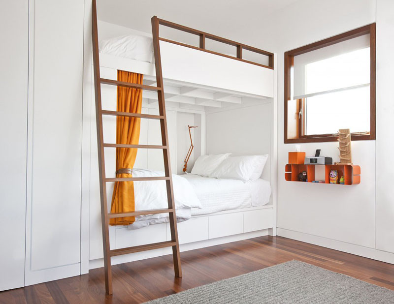 Elegant The wood ladder and frame on these white bunks perfectly matches the window frame and the orange curtains and shelf add a pop of color