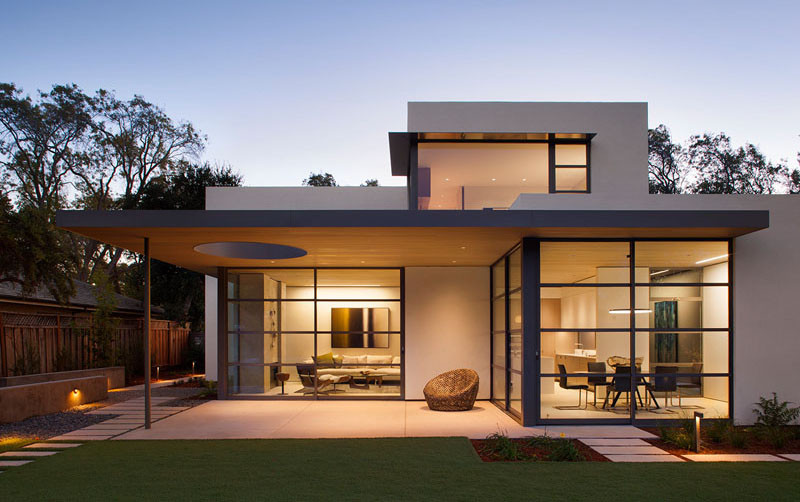This modern house has a covered patio and floor-to-ceiling glass walls.