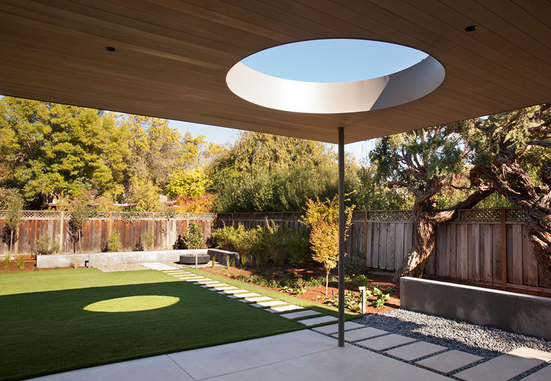This modern backyard has a patio space with a path that leads you to the corner seating area. #ModernBackyard #YardIdeas #ModernPatio
