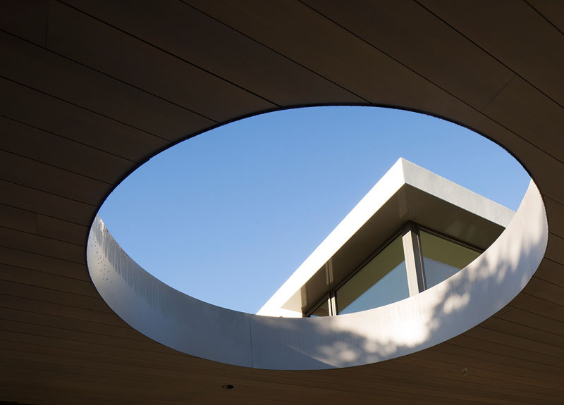 A circular opening creates a view of the sky, and at the same time, creates a distinct shadow on the grass below.